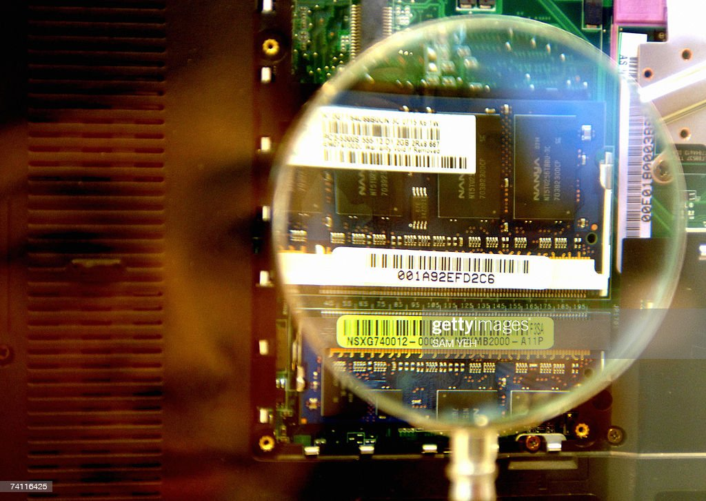 A woman looks through a magnifier to see a 2GB RAM from a notebook during the semi-tech show in Taipei 10 May 2007. Some 350 booths from 150 companies are here to demostrate their latest semiconductor products during a three-day exhibition. AFP PHOTO/Sam YEH