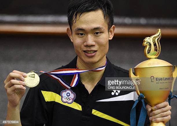 Taipei's badminton player Chia Hung Lu shows his gold medal as he holds the trophy on the podium after the Yonex BWF World Junior Championships 2015...