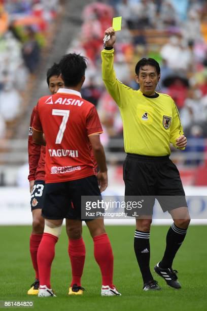Taishi Taguchi of Nagoya Grampus is shown a yellow card by referee Yuichi Nishimura during the JLeague J2 match between Nagoya Grampus and Shonan...