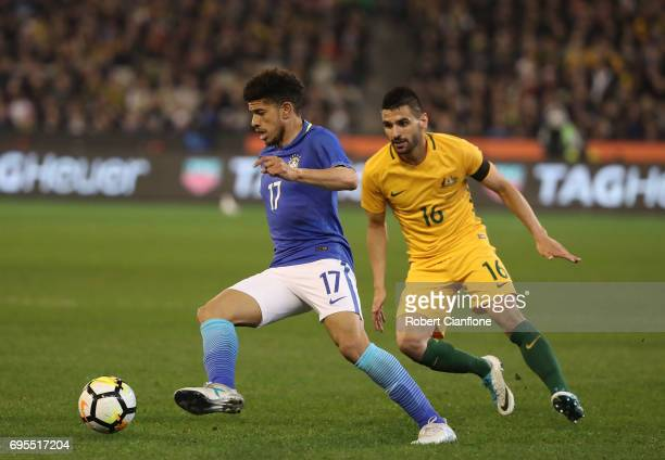 Taison Freda of Brazil is chased by Aziz Behich of Australia during the Brasil Global Tour match between Australian Socceroos and Brazil at Melbourne...