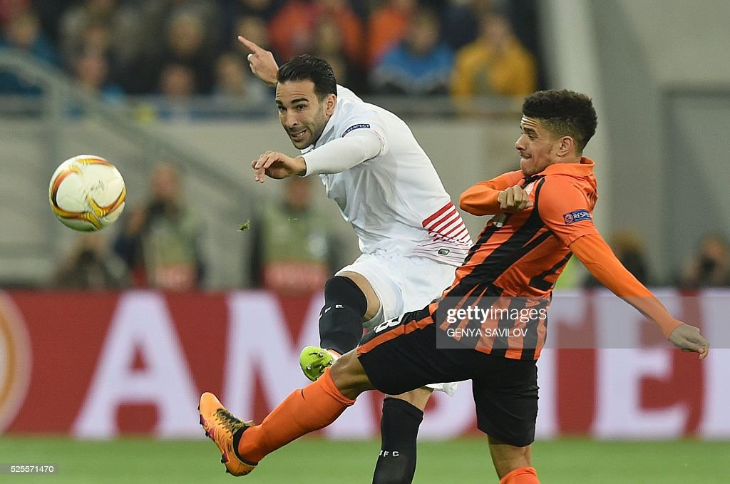 Taison (R) of FC Shakhtar vies for a ball with Adil Rami (L) of Sevilla FC during the UEFA Europa League semi-final football match FC Shakhtar Donetsk vs Sevilla FC at the Arena Lviv stadium in Lviv on April 28, 2016. / AFP / GENYA