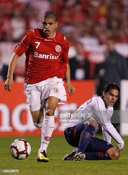 Taison of Internacional struggles for the ball with a player of Chivas during a match as part of the 2010 Copa Santander Libertadores at Beira Rio...