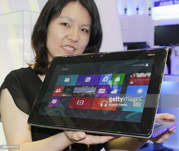TAIPEI Taiwan A woman holds the Asus Taichi ultrabook produced by Taiwan's AsusTek Computer Inc at Computex the largest computer expo in Asia and...