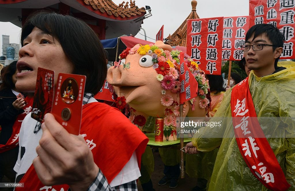Taiwan animals rights activists display a pig-shape effigy during the controversial Pig of God festival festival outside a Taoist temple in Shanhsia, the New Taipei City, on February 15, 2013. Dozens of animal rights activists protested a traditional 'holy pig' rite in which porkers are force-fed to nearly a tonne before being sacrificed in public. AFP PHOTO / Sam YEH
