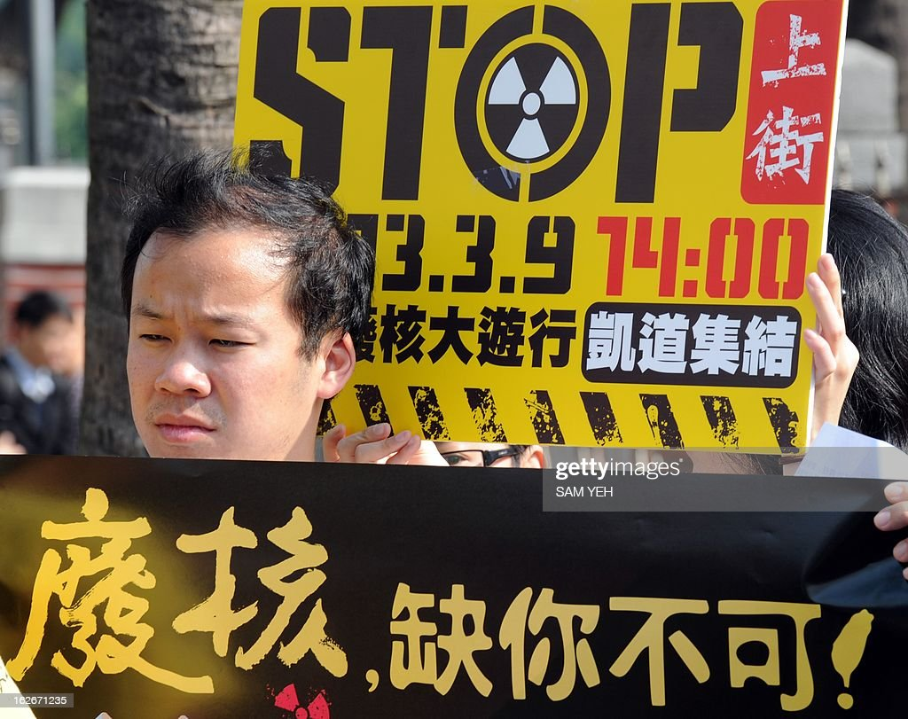 Taiwan environmental activists display placards reading 'Stop the budget for the fourth nuclear power plant' outside parliament in Taipei on February 26, 2013. Premier Jiang said for the first time that the government may support a referendum on the island's half-completed and hugely controversial fourth nuclear power plant. AFP PHOTO / Sam YEH