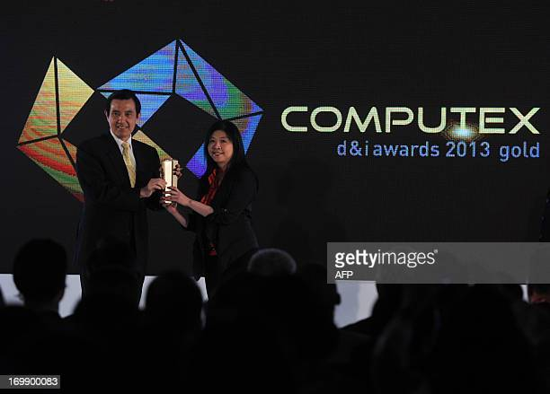 Taiwan President Ma Yingjeou hands out an award to a winning vendor staff during the 2013 Computex in Taipei on June 4 2013 Computex is Asia's...