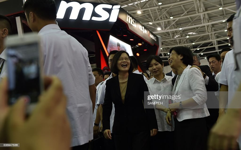 Taiwan President Tsai Ing-wen (C) laughs while visiting the annual Computex computer exhibition in Taipei on May 31, 2016. More then 5,000 booths from thirty countries take part in COMPUTEX Show between May 31 to June 4. / AFP / SAM YEH