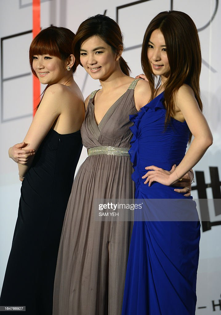 Taiwan singers from the band S.H.E. (L-R) Selina, Ella and Hebe pose for photos during a press conference in Taipei on March 28, 2013. The Taiwanese female music group S.H.E. will hold their latest live concert ' Together Forever ' between June 22-23 in Taipei. AFP PHOTO / Sam Yeh