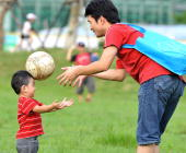 A Taiwanese boy aided by his father practices heading a football at a park in downtown Taipei on June 20 2010 AFP PHOTO/PATRICK LIN