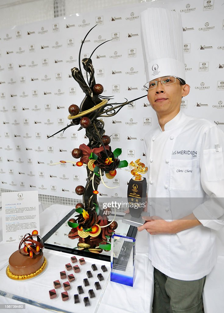 Taiwanese chef Chris Cheng his trophy and poses for photo with his chocolate creations in Taipei on November 20, 2012. Cheng won the event and will compete in the Asia-Pacific World Chocolate Masters Competition (WCM) in March 2013. AFP PHOTO / Mandy CHENG