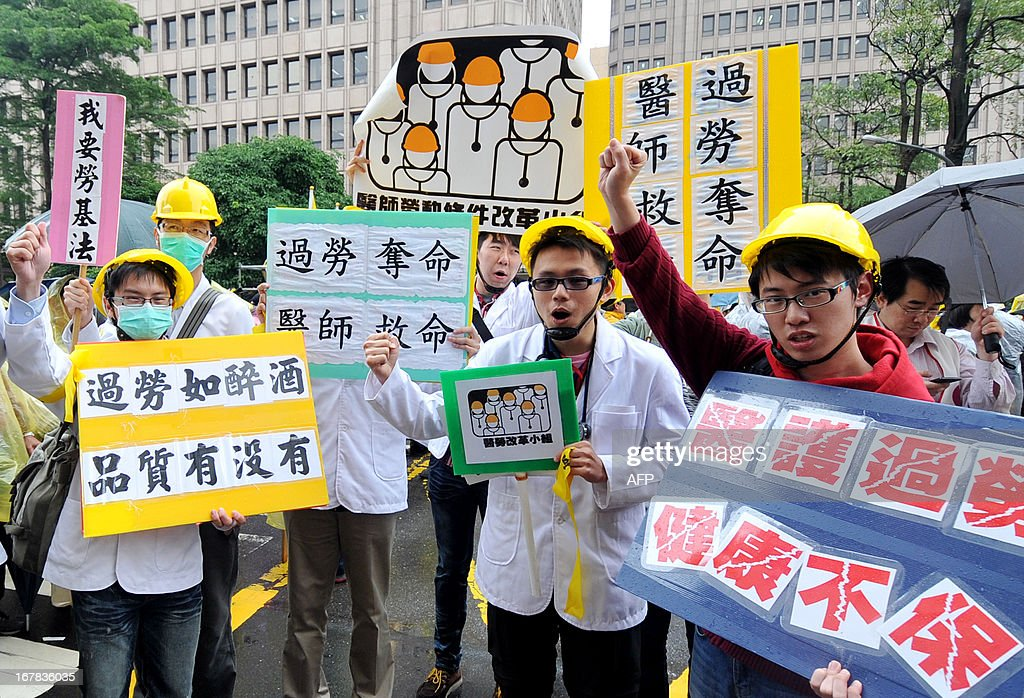 Taiwanese doctors chant slogans to protest against long working hours during a May Day rally in Taipei on May 1, 2013. More than 10,000 people took to the streets in Taipei to protest the government's planned pension cuts, including raising labour insurance fees and lowering the payment scale. AFP PHOTO / Mandy CHENG