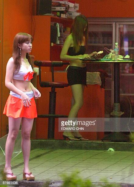 Taiwanese girl processes betel nuts while her companion hails customers at a betel nut stand in Chungho city northern Taiwan county on 15 October...