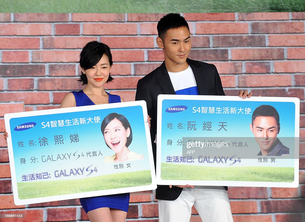 Taiwanese hostess Dee Hsu (L) and Taiwanese actor Ethan Ruan (R) both endorsers for Samsungs S4 mobile phone, pose for photos as they hold promotional banners during a press conference in Taipei on May 16, 2013. Samsung on April 26 released the latest version of its flagship Galaxy smartphone as it announced record first quarter profits driven by surging sales growth in its mobile division. AFP PHOTO / Mandy CHENG