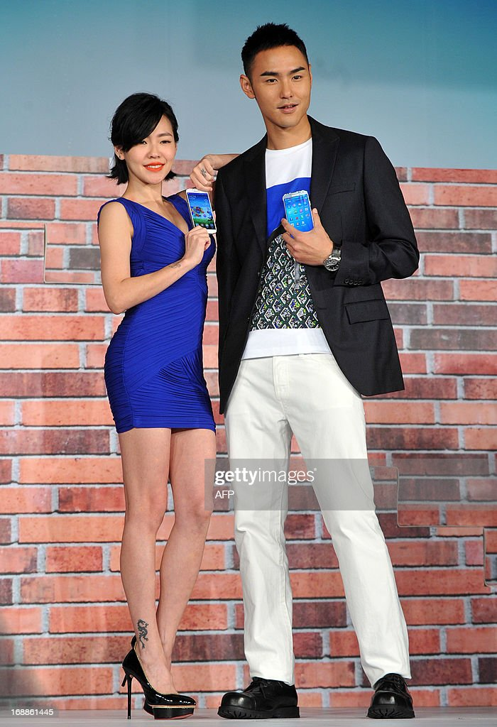 Taiwanese hostess Dee Hsu (L) and Taiwanese actor Ethan Ruan (R) hold Samsung S4 mobile phones as they pose for photos during a press conference in Taipei on May 16, 2013. Samsung on April 26 released the latest version of its flagship Galaxy smartphone as it announced record first quarter profits driven by surging sales growth in its mobile division. AFP PHOTO / Mandy CHENG