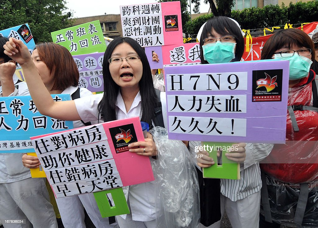 Taiwanese nurses chant slogans to protest against long working hours during a May Day rally in Taipei on May 1, 2013. More than 10,000 people took to the streets in Taipei to protest the government's planned pension cuts, including raising labour insurance fees and lowering the payment scale. AFP PHOTO / Mandy CHENG