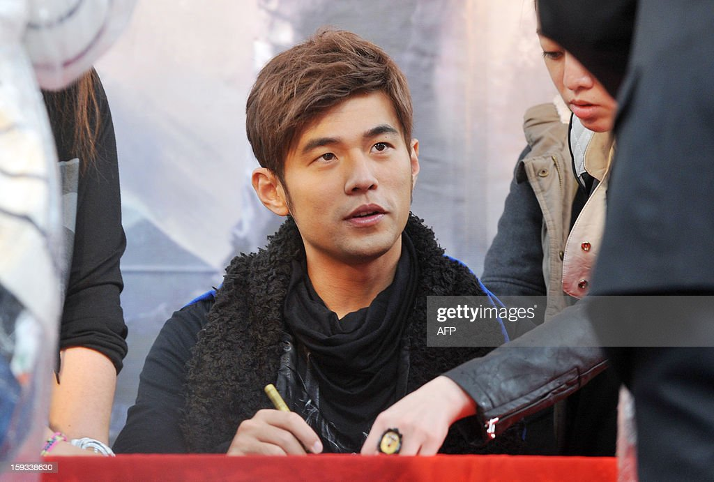 Taiwanese pop singer Jay Chou signs autographs for fans during a promotional signing event for his new album, 'Opus 12', in Taipei on January 12, 2013. Chou's new album was released on December 28, 2012. AFP PHOTO / Mandy CHENG