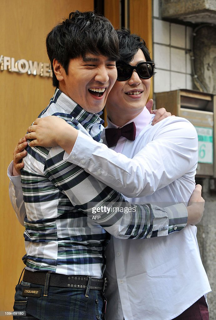 Taiwanese pop singer Ricky Xiao (R) and Taiwanese actor Mark Chao (L) hug during a music video shoot for television of the album title track 'Ricky is a nice guy' in Taipei on January 14, 2013. Xiao's new album will be released on January 30, 2013. AFP PHOTO / Mandy CHENG