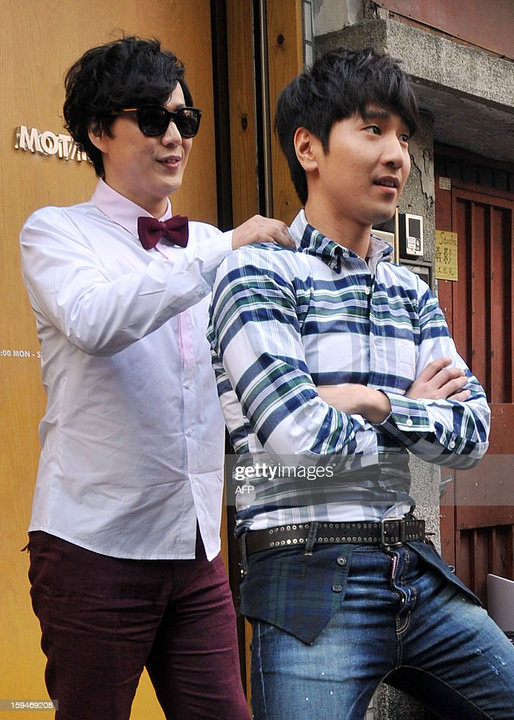 Taiwanese pop singer Ricky Xiao (L) massages the shoulders of Taiwanese actor Mark Chao (R) during a music video shoot for television of the album title track 'Ricky is a nice guy' in Taipei on January 14, 2013. Xiao's new album will be released on January 30, 2013. AFP PHOTO / Mandy CHENG