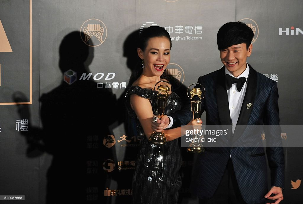 Taiwanese singer Julia Peng (L) and Singaporean singer-songwriter JJ Lam (R) display their trophies after winning the Best of Male and Female Singer Awards at the 27th Golden Melody Awards in Taipei on June 25, 2016. Some of Mandarin pop's biggest names have gathered for the annual Golden Melody music awards, with singers, songwriters and composers from Taiwan, China, Hong Kong, Singapore and Malaysia competing in more than 20 categories. / AFP / SANDY