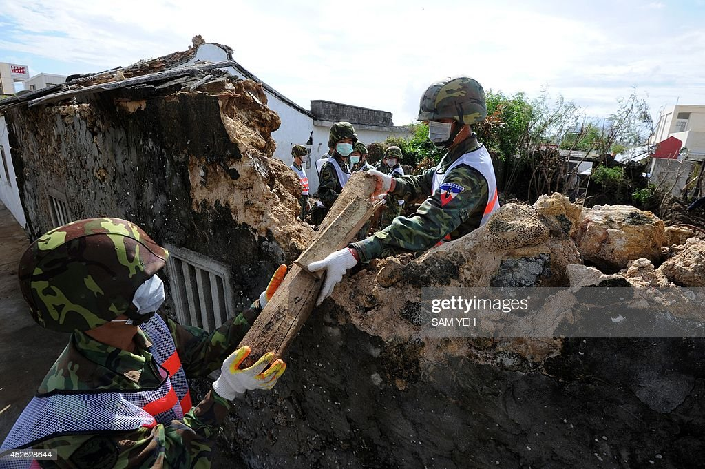 Taiwanese soldiers help clean up the site where TransAsia Airways flight GE222 crashed on July 23 in poor weather near the airport at Magong on the...