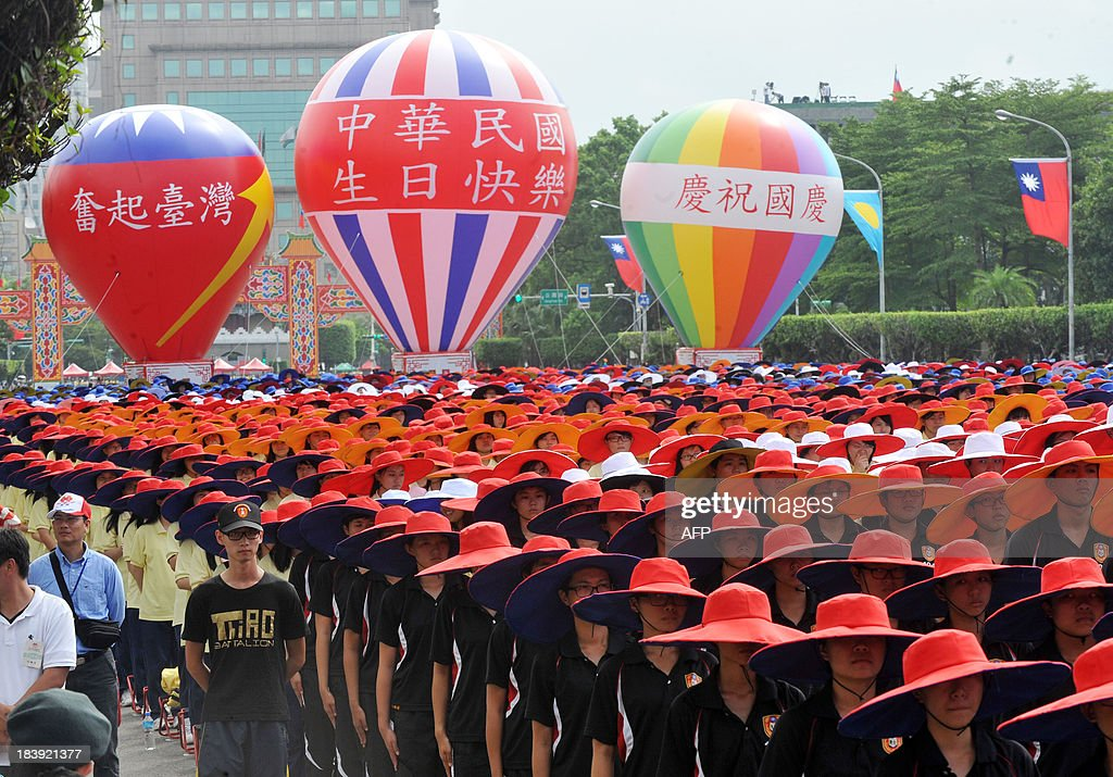 Taiwanese students wearing colourful costumes and hats parade during celebrations to mark National Day in Taipei on October 10, 2013. Taiwan President Ma Ying-jeou on October 10 hailed a new trade pact with China as protesters hurled shoes and carried a mock coffin to oppose the deal and demand his resignation. AFP PHOTO / Mandy CHENG