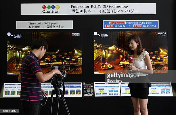 A Taiwanese television crew reports in front of Sharp Corp televisions displayed inside the Sakai Display Products Corp plant in Sakai City Osaka...