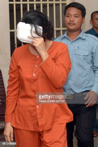 Taiwanese woman Lin Yu Shin covers her face as she is escorted by a Cambodian prison guard at the Phnom Penh Municipal court on April 29 2014 A...