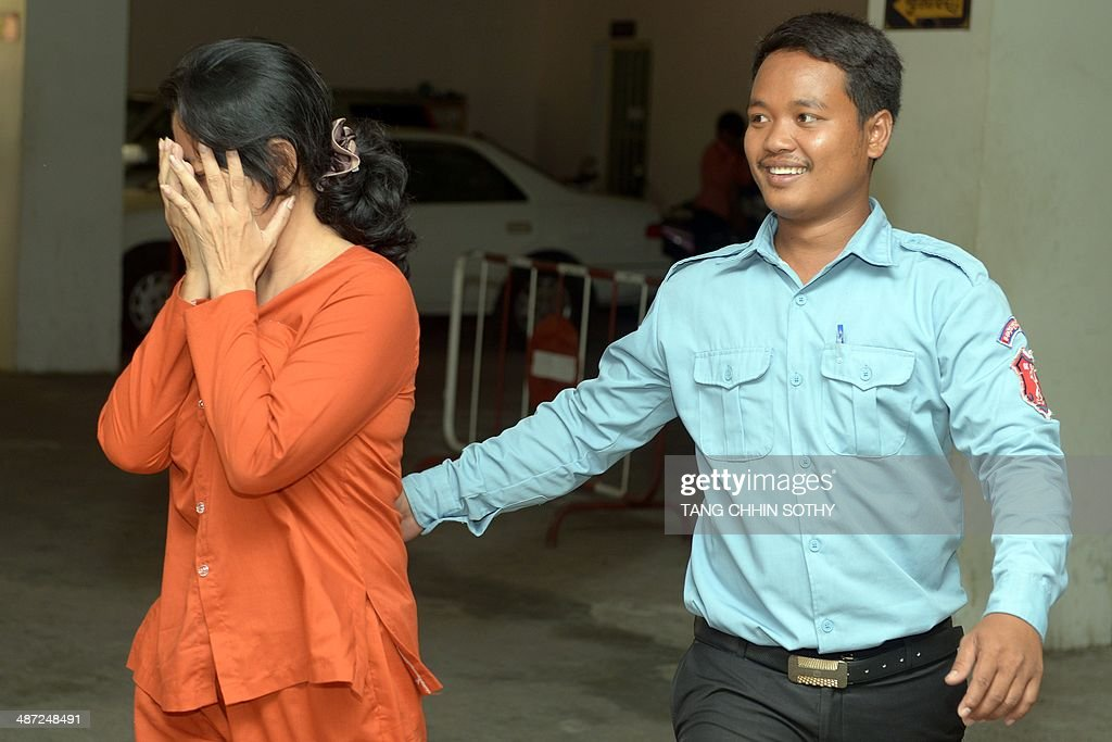 Taiwanese woman Lin Yu Shin (L) covers her face as she is escorted by a Cambodian prison guard (R) at the Phnom Penh Municipal court on April 29, 2014. A Taiwanese woman and her five associates were sentenced to 10 years in jail each for trafficking hundreds of Cambodians to work in slave-like conditions on fishing boats off Africa. AFP PHOTO/ TANG CHHIN SOTHY