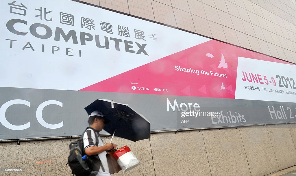 Taiwan-IT-technology-show,ADVANCER by Benjamin Yeh This photo taken on June 3, 2012 shows a man walking past a huge billboard featuring Computex, Asia's leading IT trade fair, outside the venue in Taipei. The five-day Computex, an annual tech extravaganza in Taipei now in its 32nd year, will provide one of the most comprehensive glimpses yet of the next version of the world's dominant software. AFP PHOTO / Mandy CHENG