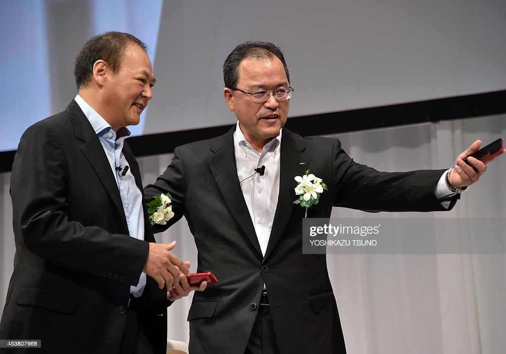 Taiwan's electronics maker HTC CEO Peter Chou speaks with Japan's telecommunications giant KDDI president Takashi Tanaka as they introduce the new...