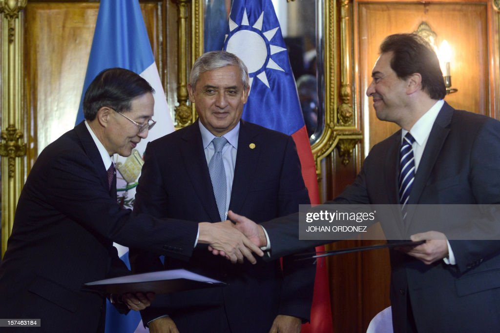Taiwan's Foreign Minister David Lin (L) shakes hands with his Guatemalan counterpart Harold Caballeros, as Guatemalan President Otto Perez Molina (C) looks on, during the signing of aid agreements to Guatemala at the presidential residence in Guatemala City on December 3, 2012. AFP PHOTO/Johan ORDONEZ