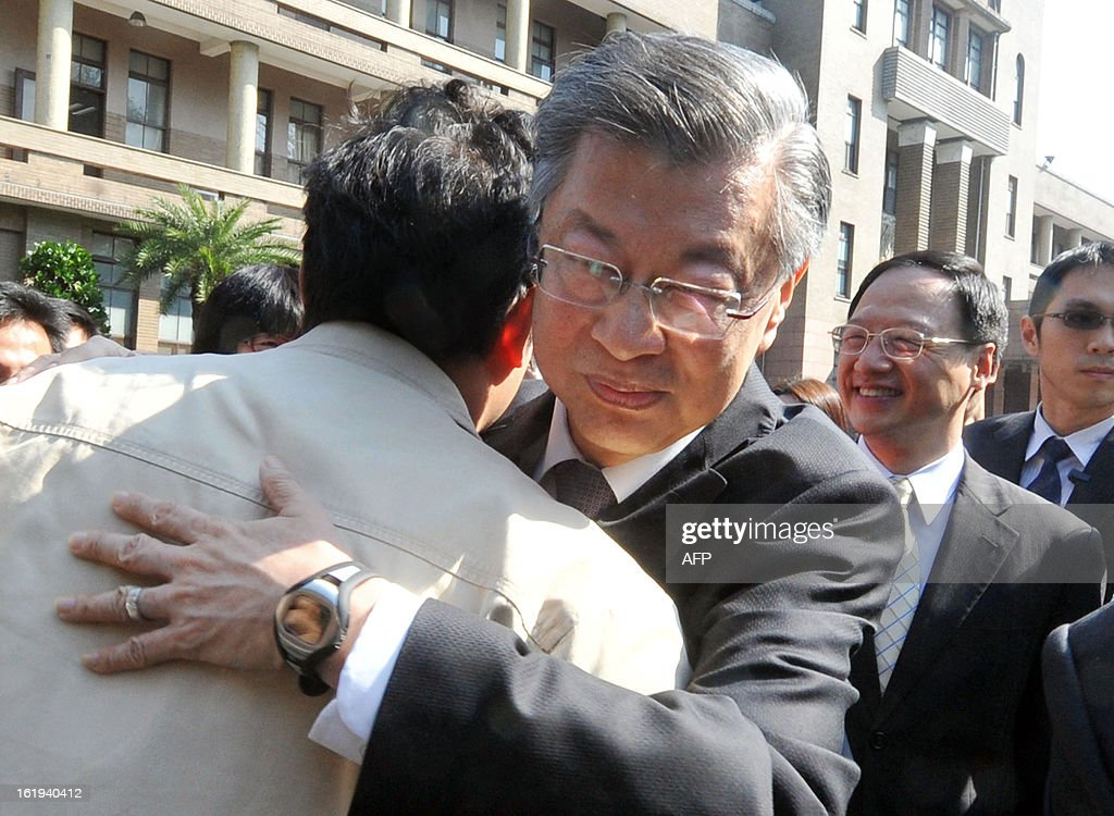 Taiwan's former premier Sean Chen (C) hugs an official seeing him off as new Premier Jiang Yi-huah (2nd R) smiles following an oath-taking ceremony for the new cabinet in Taipei on January 18, 2013. A new cabinet was sworn in following a reshuffle touted by President Ma Ying-jeou as adding new skills and capability to his government. AFP PHOTO / Mandy CHENG