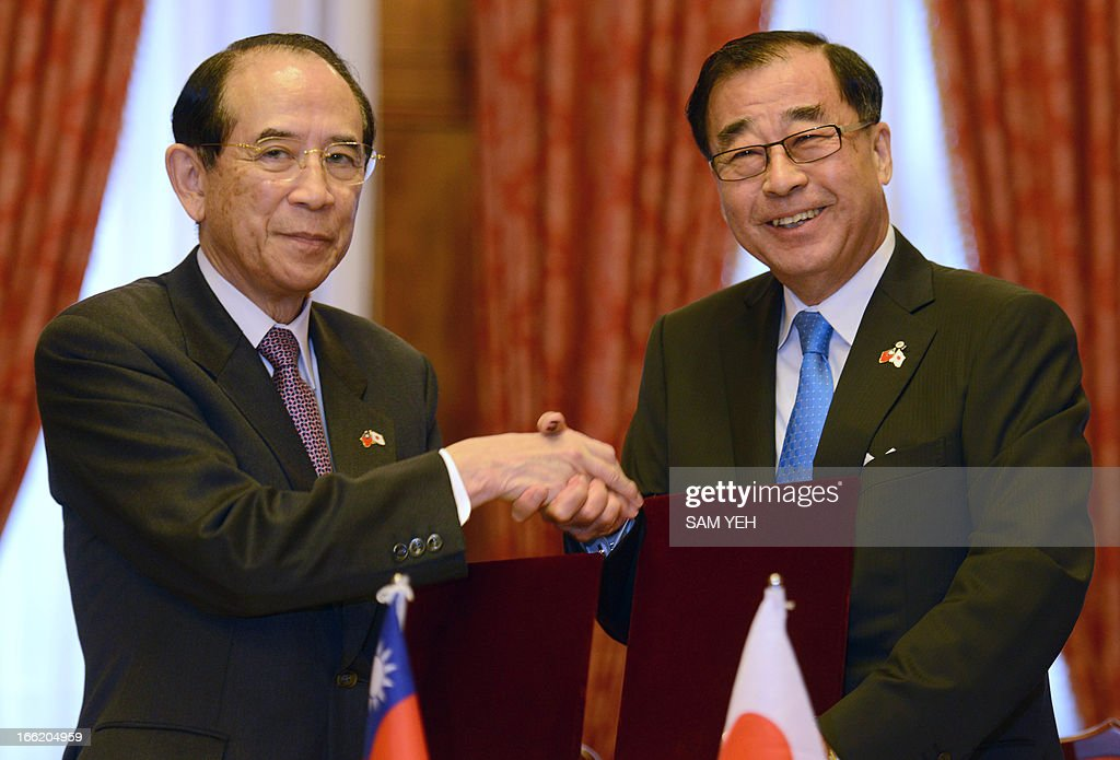 Taiwan's Liao Liao-yi (R), the head of the Association of East Asian Relations shakes hands with Japan's Mitsuo Ohashi, head of the Interchange Association after a signing ceremony in Taipei on April 10, 2013. Taiwan and Japan arrived at a hard-won agreement on fishing rights near islands at the centre of a territorial row that has soured ties between Beijing and Tokyo, officials said. AFP PHOTO/ Sam Yeh