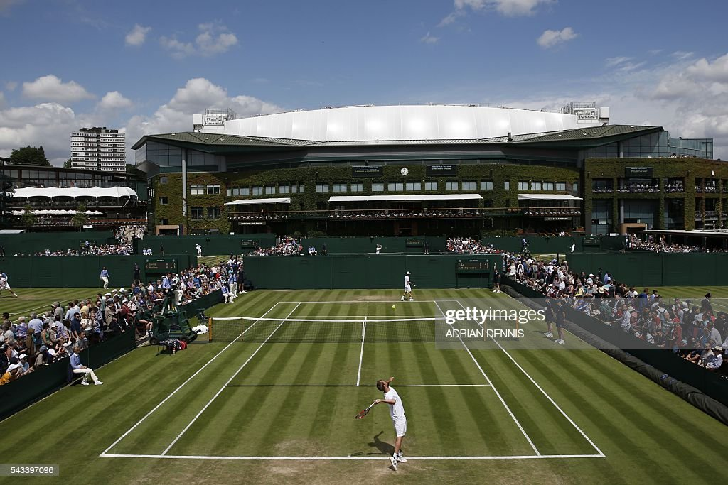 Taiwan's Lu Yen-Hsun and Russia's Alexander Kudryavtsev warm up for their men's singles first round match on the first day of the 2016 Wimbledon Championships at The All England Lawn Tennis Club in Wimbledon, southwest London, on June 28, 2016. / AFP / ADRIAN