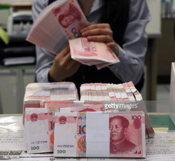 A Taiwan's Mega Bank staff counts Chinese yuan banknotes in Taipei on February 6 2013 Taiwanese banks started allowing customers to open Chinese yuan...