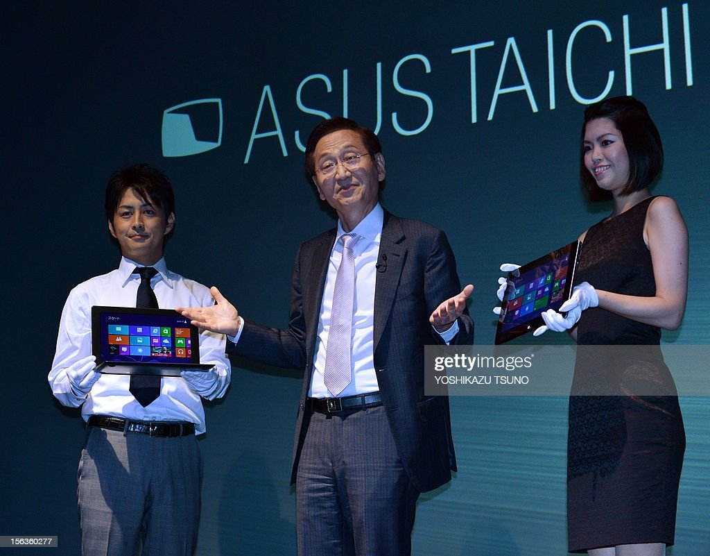 Taiwan's personal computer giant ASUS chairman Honney Shih (C) displays the world's first dual screens notebook computer 'Taichi', which has 11.6-inch LCD display on the both side, enabling to use as a tablet and notebook computer in Tokyo on November 14, 2012. The unique PC, equipped with Intel's Core i7 processor on its CPU will go on sale December 8. AFP PHOTO / Yoshikazu TSUNO