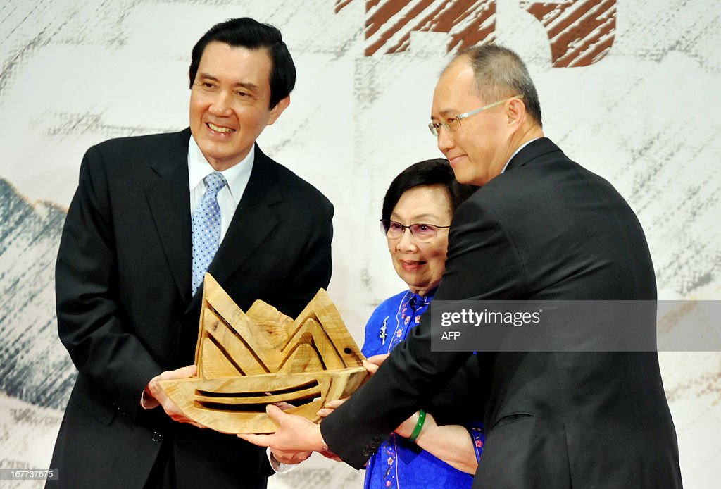Taiwan's President Ma Ying-jeou (L) confers a gift to Cecilia Koo, widow of the island's former chief negotiator with China Koo Chen-fu, during a ceremony held at the headquarters of the island's quasi-official Straits Exchange Foundation in Taipei on April 29, 2013. Ma renewed the 'one China' policy of his government as Taiwan marked the 20th anniversary of the of the first high-level talks between Taiwan and the Chinese mainland since their split in 1949 at the end of a civil war. AFP PHOTO / Mandy CHENG