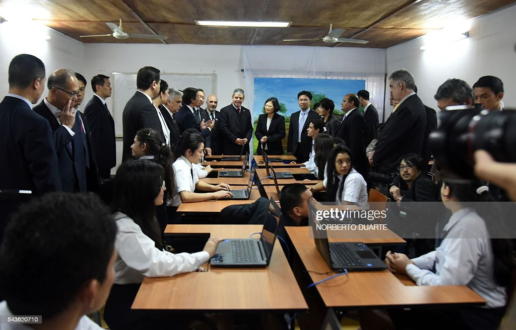 Taiwan's President Tsai Ing-wen (C, right), accompanied by Paraguayan Education Minister Enrique Riera (C, left), visits the General Andres Rodriguez school to which the country donated computers, in Asuncion on June 29, 2016. Taiwan's new president is visiting Paraguay as part of her first overseas trip since taking office in May. / AFP / NORBERTO