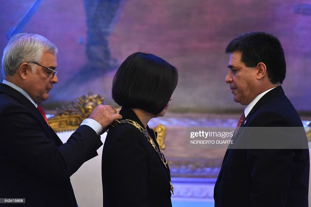 Taiwan's President Tsai Ing-wen (C) is decorated by Paraguayan President Horacio Cartes (R) with the Marshal Francisco Solano Lopez Honour Medal, during a ceremony at the presidential palace in Asuncion on June 28, 2016. Taiwan's new president is visiting Paraguay as part of her first overseas trip since taking office in May. / AFP / NORBERTO