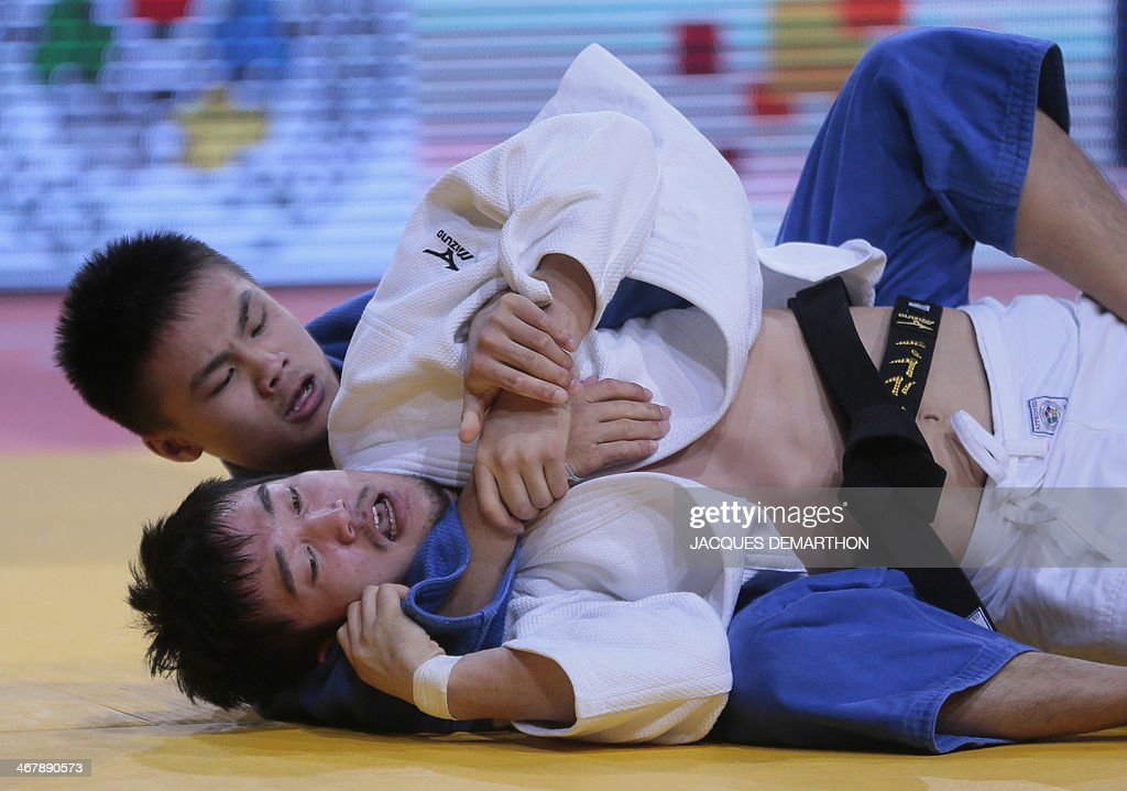 Taiwan's Tsai Ming Yen in blue attempts a strangle on Mongolia's Kherlen Ganbold in white during the 60kg bronzemedal fight at the 2014 Paris Judo...