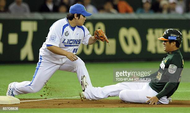 Taiwan's UniPresident 7Eleven Lions outfielder Pan WuHsiung slides onto the third base as Japan's Saitama Seibu Lions third baseman Takeya Nakamura...