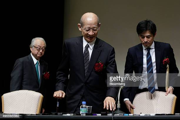 Taizo Nishimuro president of Japan Post Holdings Co center and Masatsugu Nagato president of Japan Post Bank Co left arrive for a news conference...