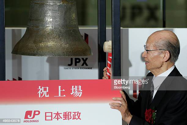 Taizo Nishimuro president of Japan Post Holdings Co strikes a bell during a ceremony to launch the company's listing on the Tokyo Stock Exchange in...