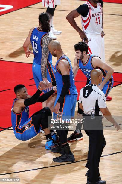 Taj Gibson and Alex Abrines help up Russell Westbrook of the Oklahoma City Thunder during the game against the Houston Rockets in Game Five of the...