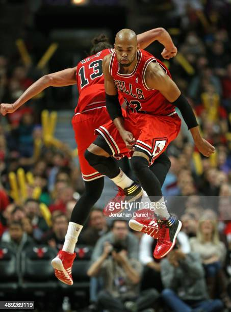 Taj Gibson and Joakim Noah of the Chicago Bulls celebrate during a timeout against the Brooklyn Nets at the United Center on February 13 2014 in...
