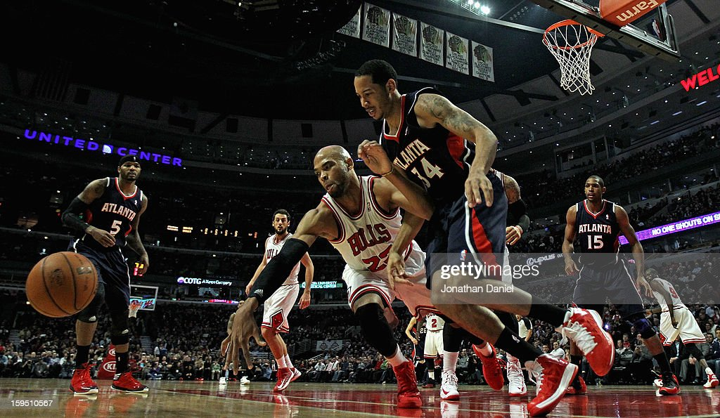 Taj Gibson #22 of the Chicago Bulls and Devin Harris #34 of the Atlanta Hawks chase down a loose ball at the United Center on January 14, 2013 in Chicago, Illinois.