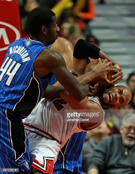 Taj Gibson of the Chicago Bulls battles for a rebound with Andrew Nicholson of the Orlando Magic at the United Center on December 16 2013 in Chicago...