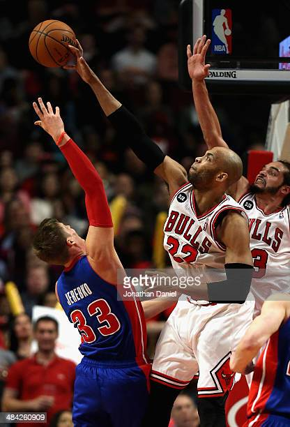 Taj Gibson of the Chicago Bulls blocks a shot by Jonas Jerebko of the Detroit Pistons at the United Center on April 11 2014 in Chicago Illinois The...