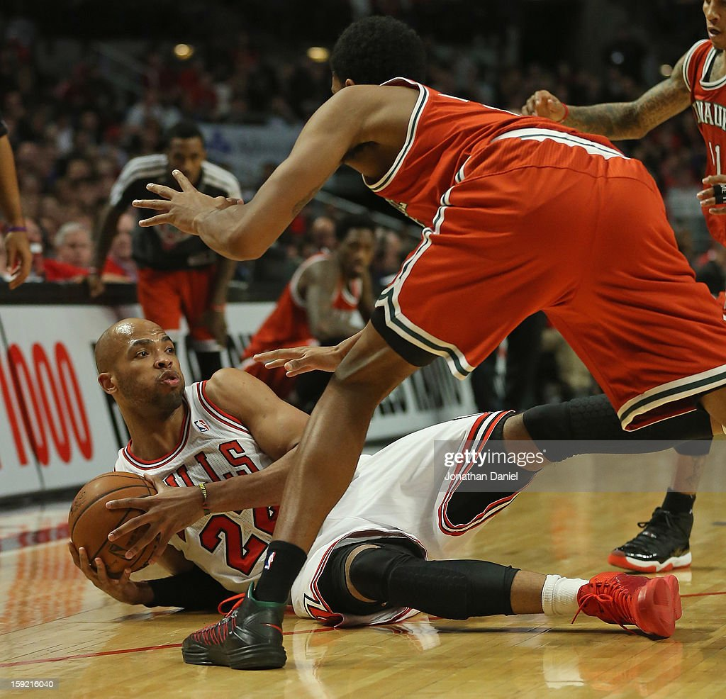 Taj Gibson #22 of the Chicago Bulls controls a loose ball on the ground as Ekpe Udoh #13 of the Milwaukee Bucks stands over him at the United Center on January 9, 2013 in Chicago, Illinois. The Bucks defeated the Bulls 104-96.