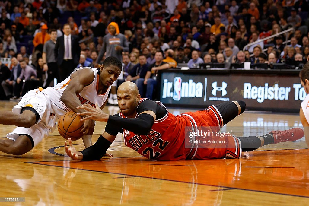 Taj Gibson of the Chicago Bulls dives for a loose ball with Brandon Knight of the Phoenix Suns during the NBA game at Talking Stick Resort Arena on...